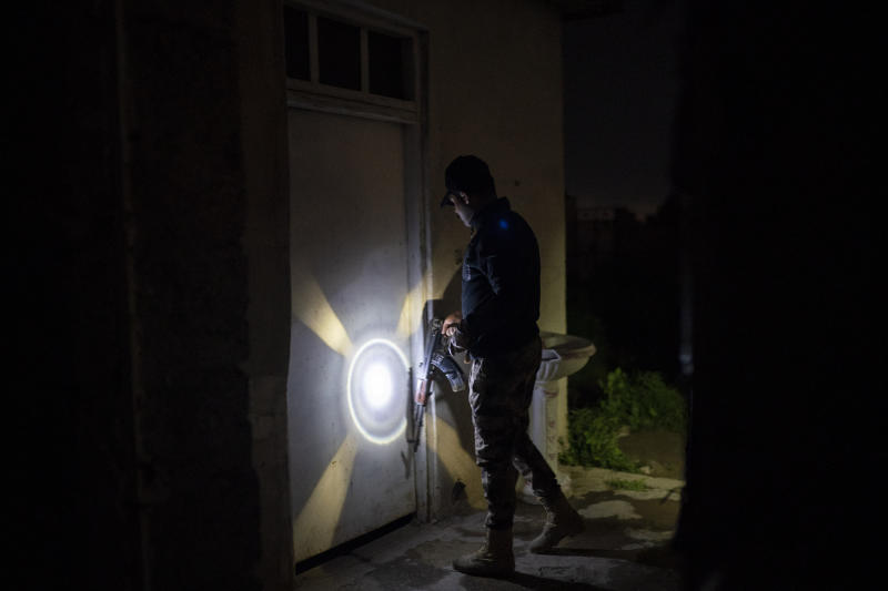 In this April 2, 2019 photo, an Iraqi army 20th division soldier uses his AK-47 rifle to knock on a door during a nighttime raid near Badoush, Iraq. A year and a half after the Islamic State group was declared defeated in Iraq, the northern Iraqi town is a key battleground between security forces trying to stamp out the group's remnants and the militants who have reverted to insurgency. (AP Photo/Felipe Dana)