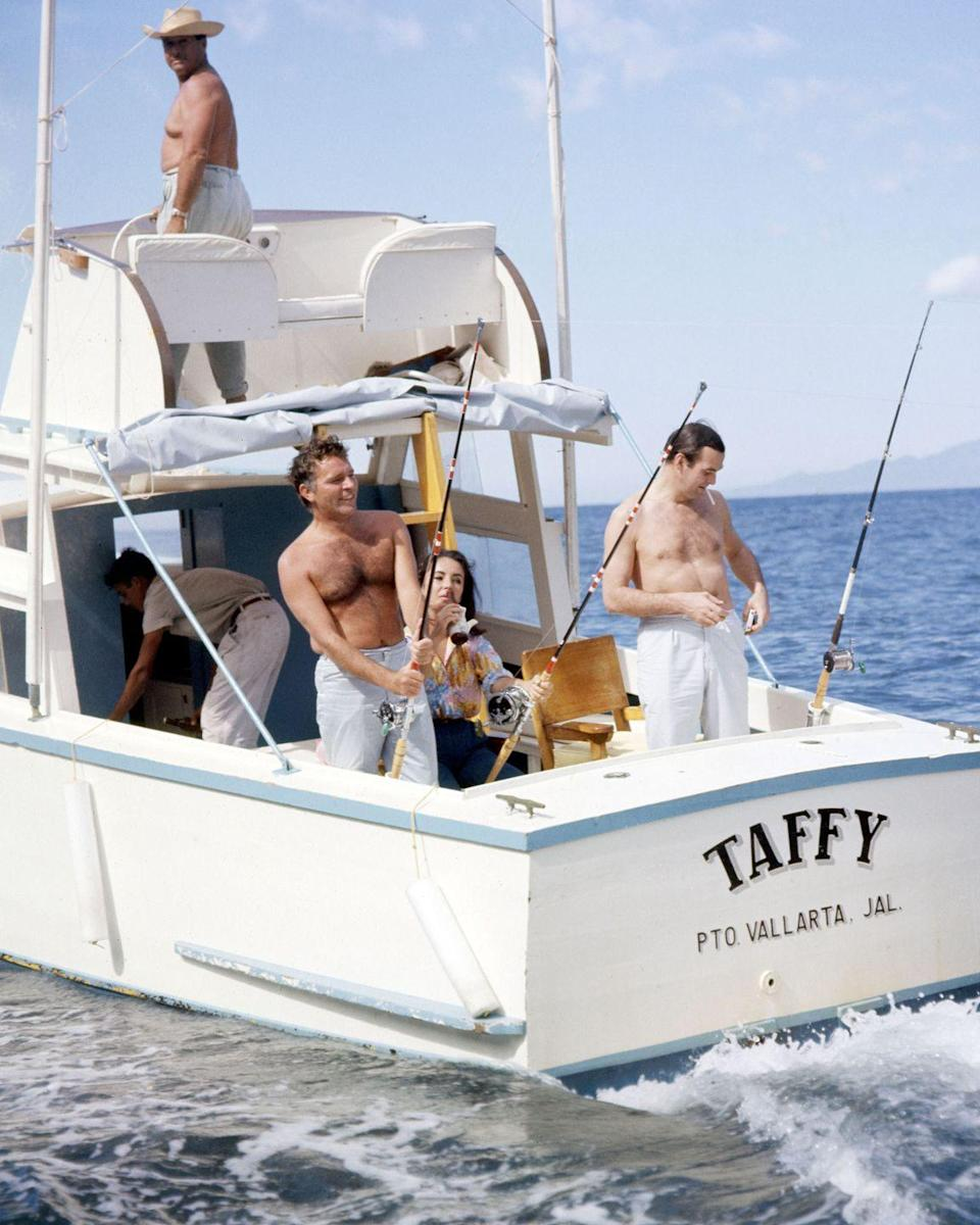<p>Richard Burton with his wife, Elizabeth Taylor, and Stanley Baker on a fishing trip in Burton's boat off the coast of Mexico. </p>