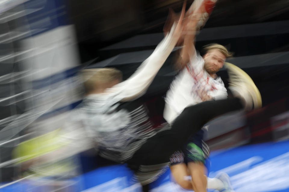 In this long exposure photo, Norway's Petter Overby scores past Iceland's Viktor Gisli Hallgrimsson during the World Handball Championship between Iceland and Norway in Cairo, Egypt, Sunday, Jan. 24, 2021. (AP Photo/Petr David Josek, Pool)