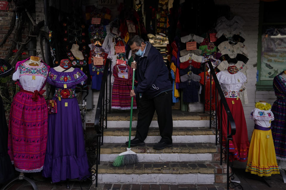 Victor Flores, 66, a third-generation owner of a gift shop, sweeps the steps of his store on Olvera Street in downtown Los Angeles, Wednesday, Dec. 16, 2020. The tree-covered brick alley typically teeming with tourists is empty. Many of the shops that sell everything from traditional Mexican folk dresses to paintings of artist Frida Kahlo to sombreros are padlocked and the open ones have few, if any, customers. (AP Photo/Jae C. Hong)