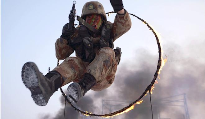 A PLA soldier jumps through a ring of fire during a military exercise in Shihezi in the Xinjiang region early this month. Photo: Reuters