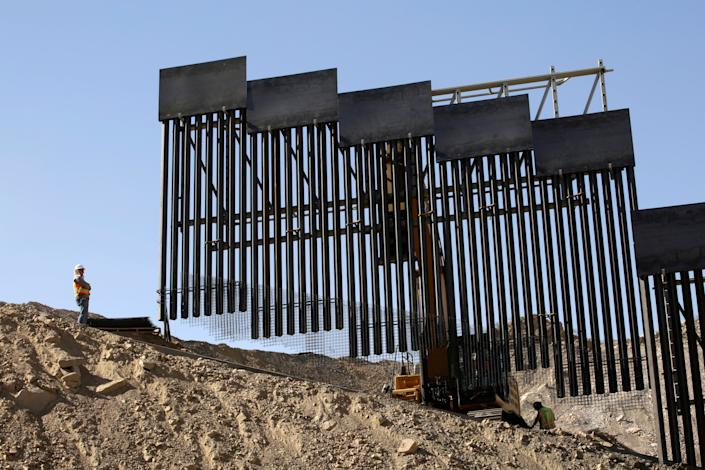A construction crew works on a private border wall