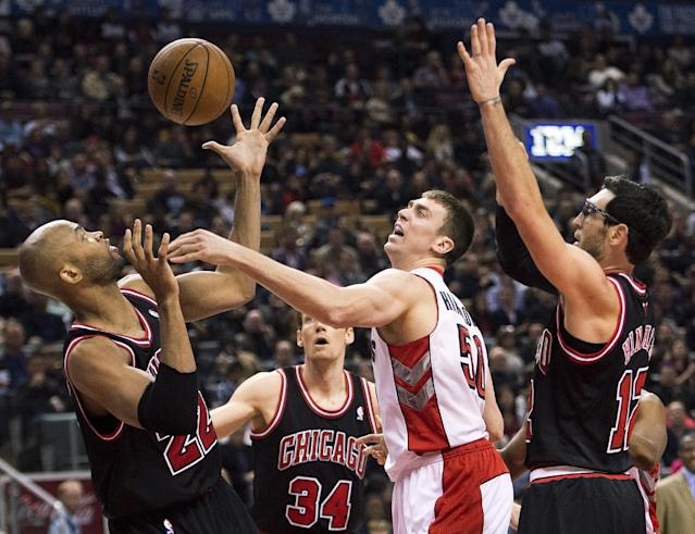 Toronto Raptors forward Tyler Hansbrough, center, battles for the loose ball against Chicago Bulls' Taj Gibson, left, and Kirk Hinrich, right, during first-half NBA basketball game action in Toronto, Friday, Nov. 15, 2013. (AP Photo/The Canadian Press, Nathan Denette)