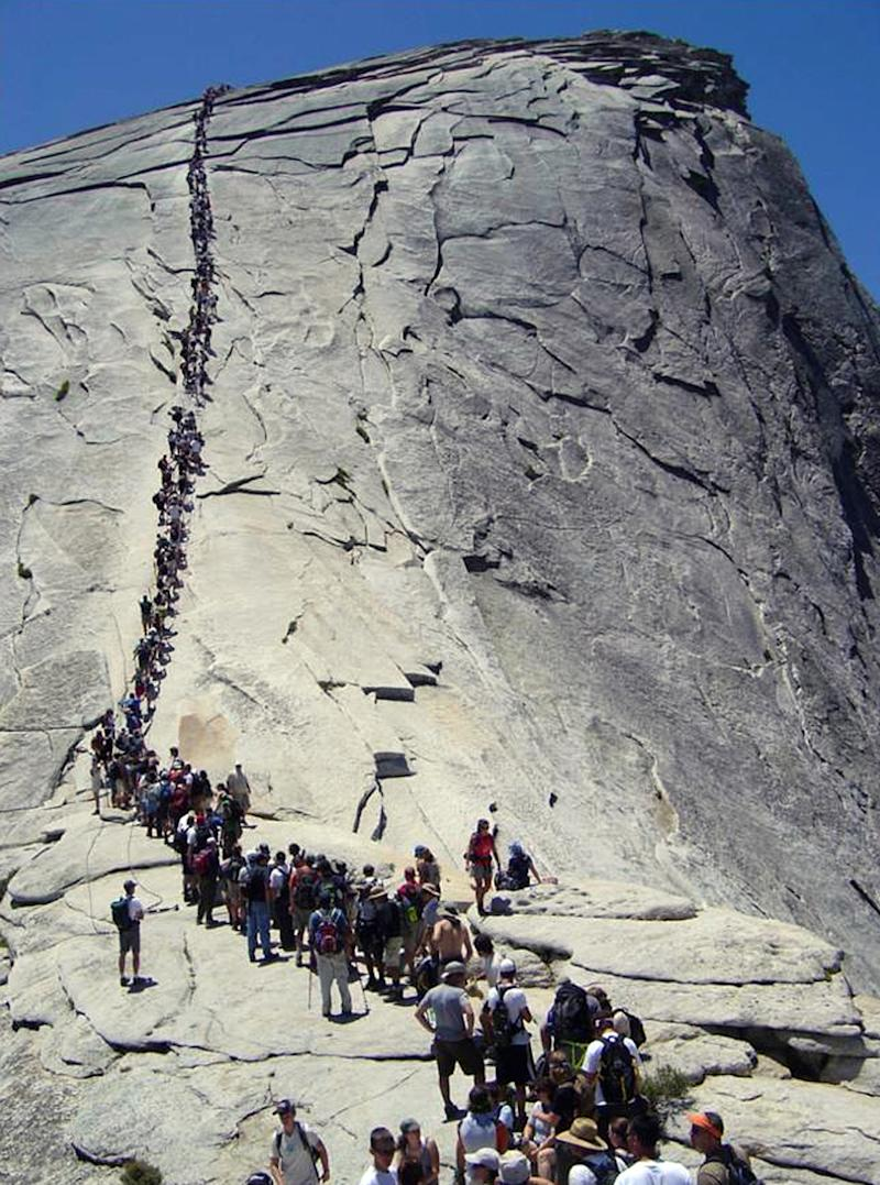In this 2006 photo provided by the National Park Service, tourists climb Half Dome at Yosemite National Park, Calif. A climb up Half Dome was once only for the most seasoned outdoors people, but in recent years tourists and weekend warriors have been scaling the steep granite slope with the aid of steel cables. When daily traffic on the route reached 1,200 in 2009 and hikers routinely backed up like cars at rush hour, park officials realized something had to be done.  (AP photo/National Park Service)