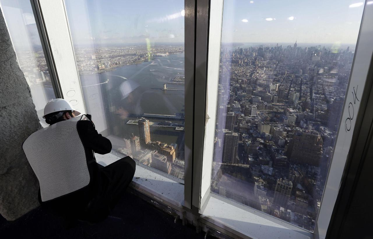 A member of the media takes a photograph of the Manhattan skyline from the unfinished observation deck on the 100th floor of the One World Trade Center building, under construction in New York, Tuesday, April 2, 2013. The observation deck will occupy the tower's 100th through 102nd floors. Elevators will whisk visitors to the top in just one minute but the experience of visiting the attraction will take an hour. (AP Photo/Richard Drew)
