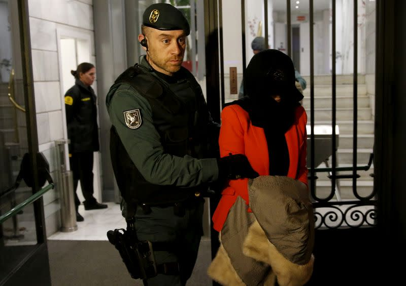 FILE PHOTO: A suspect is led by a Spanish Civil Guard officer as they leave the headquarters of Industrial and Commercial Bank of China (ICBC) during a raid in Madrid