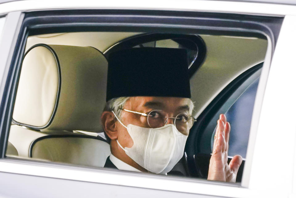 Malaysia's King Sultan Abdullah Sultan Ahmad Shah waves as he leaves National Palace in Kuala Lumpur, Malaysia, Sunday, Oct. 25, 2020. National Palace statement says Malay rulers has decided not to accede to Prime Minister Muhyiddin Yassin's request to declare a state of emergency. (AP Photo/Vincent Thian)