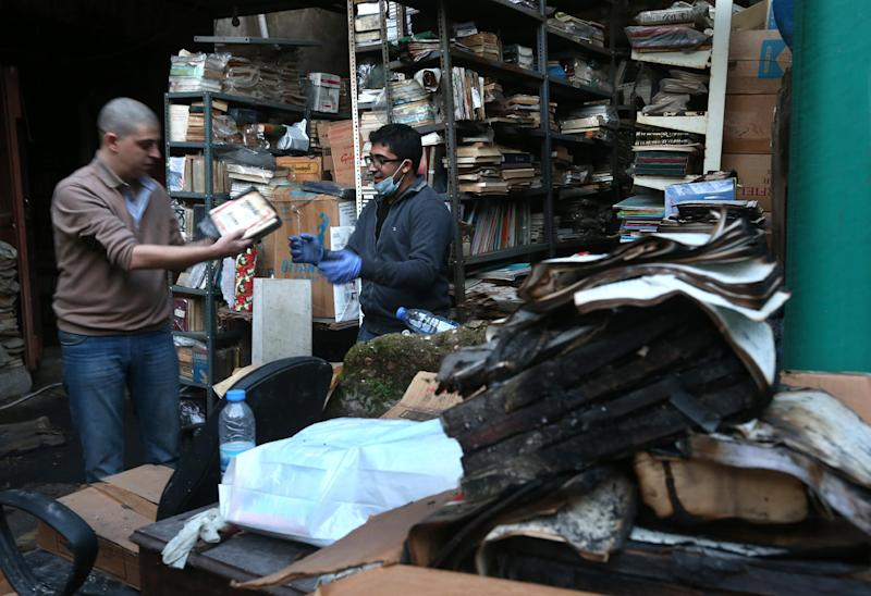 In this picture taken on Sunday, Jan. 5, 2014, Lebanese activists remove burned books, at the Saeh (Tourist) Library which was set on fire by masked men, in the northern city of Tripoli, Lebanon. Books that were burnt in an arson attack targeting a crammed, chaotic and popular library in the northern Lebanese city of Tripoli have become the latest victim of the country's rising sectarian tensions.(AP Photo/Hussein Malla)