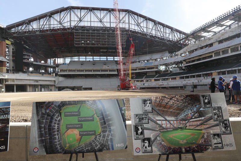 Illustrations in the foreground show information about the under construction baseball field at the new Texas Rangers stadium in Arlington, Texas, Wednesday, Dec. 4, 2019. The dimensions at the new Texas Rangers' ballpark will mark the jersey numbers that have been retired by the team. (AP Photo/LM Otero)
