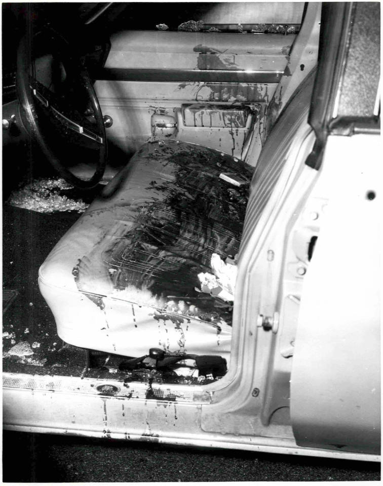 """This undated black and white photo released by the U.S. Attorney's Office and presented as evidence Wednesday, June 19, 2013, during the trial of James """"Whitey"""" Bulger in U.S. District Court in Boston, shows a car with a blood-stained front seat and shattered glass on the floorboard. Bulger, the reputed former head of the mostly Irish-American Winter Hill Gang based in South Boston, is accused of playing a role in 19 killings during the 1970s and '80s. (AP Photo/U.S. Attorney's Office)"""