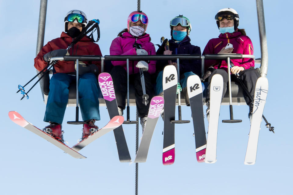 FILE - In this Oct. 30, 2020 file photo skiers wearing face masks riding a chairlift on the opening day of the Verbier ski area in the Swiss Alps, EU member states Austria, France, Germany and Italy are shutting or severely restricting access to the slopes this holiday season amid COVID-19 concerns, Switzerland is not. (Jean-Christophe Bott/Keystone via AP, File)