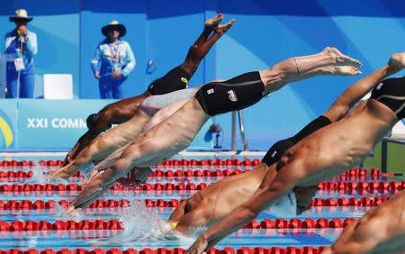 Swimming - Gold Coast 2018 Commonwealth Games - Men's 50m Freestyle - Heats - Optus Aquatic Centre - Gold Coast, Australia - April 9, 2018. Benjamin Proud (in red cap) of England dives into the water with fellow competitors during heat 8 of the men's 50m freestyle competition. REUTERS/David Gray
