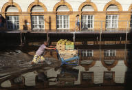 A man pushes a shopping cart loaded with bananas through a street flooded by the Negro River in downtown Manaus, Amazonas state, Brazil, on Tuesday, June 1, 2021. Rivers around Brazil's biggest city in the Amazon rain forest have swelled to levels unseen in over a century of record-keeping, according to data published Tuesday by Manaus' port authorities. (AP Photo/Edmar Barros)
