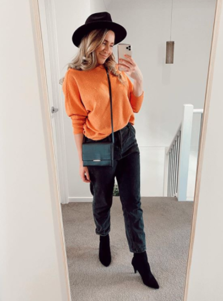 Woman in black jeans, a black hat and orange jumper