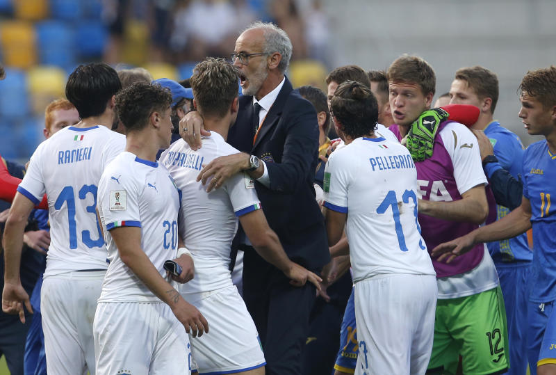 Italy coach Paolo Nicolato separates Italy and Ukraine players at the end of the semi final match between Ukraine and Italy at the U20 World Cup soccer in Gdynia, Poland, Tuesday, June 11, 2019. (AP Photo/Darko Vojinovic)