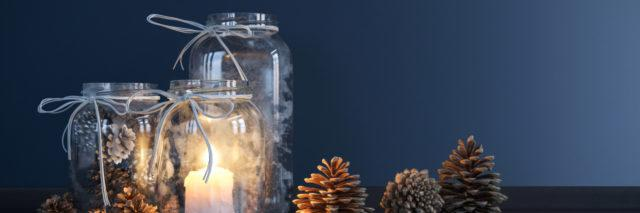 Mason jars with candles and decorative pine cones.