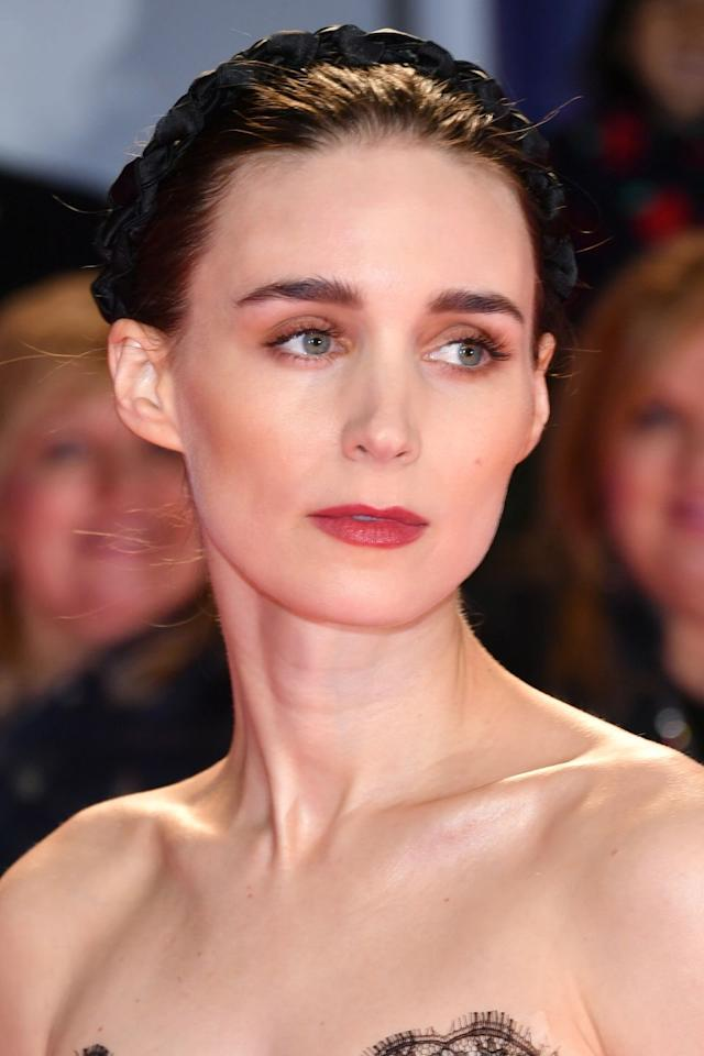 """<p>Rooney Mara's romantic red carpet beauty look was designed to look """"just like a painting"""", according to her make-up artist <a href=""""https://www.instagram.com/melaniemakeup/?hl=en"""" target=""""_blank"""">Mélanie Inglessis</a>. Inglessis used Tom Ford's <a href=""""https://www.harveynichols.com/brand/tom-ford/670235-brow-sculptor/p3041814/?istCompanyId=c721e458-728e-4a28-bc83-6a1d2abf7708&istFeedId=8676b250-53e7-4523-a1d2-57bcefdf5980&istItemId=itiqiqqxa&istBid=tzxt&gclid=CjwKCAjwtuLrBRAlEiwAPVcZBnyPxhWAs3bpykDx7hWvW5euAX9U6ZKFCWPrQxL40OzypWxCJVicXRoC180QAvD_BwE&gclsrc=aw.ds"""" target=""""_blank"""">Eyebrow Pencil</a> and a <a href=""""https://www.harpersbazaar.com/uk/beauty/make-up-nails/news/g21878/best-mascaras/"""" target=""""_blank"""">lash-lengthening mascara</a> to define the actress' eyes, combined with a rose pink lipstick, like Bobbi Brown's <a href=""""https://www.net-a-porter.com/gb/en/product/1041143?"""" target=""""_blank"""">Lip Colour in Rose Petal</a>. The hairstylist <a href=""""https://www.instagram.com/hairbyadir/?hl=en"""" target=""""_blank"""">Adir Abegal</a> then accessorised her scraped-back bun with a black twisted headband, like those from <a href=""""https://www.mytheresa.com/en-gb/jennifer-behr-lorelei-plaited-silk-headband-1230278.html?"""" target=""""_blank"""">Jennifer Behr</a>.<br></p>"""