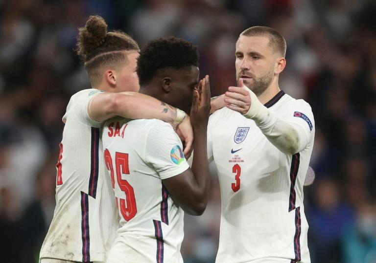 England's football team has united against raciism, Here midfielder Bukayo Saka (c) is consoled after failing to score in the penalty shootout of the Eur2020 final which England lost against Italy on Sunday