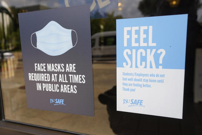 Face mask requirements are posted at the various entrances at the Rose E. McCoy Auditorium where COVID-19 vaccinations are being offered on the Jackson State University campus in Jackson, Miss., Tuesday, July 27, 2021. The university has similar signage posted throughout the campus. The Centers for Disease Control and Prevention announced new recommendations that vaccinated people return to wearing masks indoors in parts of the U.S. where the coronavirus is surging and also recommended indoor masks for all teachers, staff, students and visitors to schools, regardless of vaccination status. (AP Photo/Rogelio V. Solis)