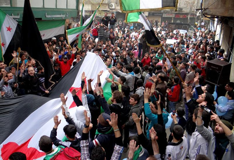 """In this citizen journalism image provided by Aleppo Media Center AMC which has been authenticated based on its contents and other AP reporting, anti-Syrian regime protesters raise up their hands as they wave Syrian revolutionary flags during a protest to mark the second anniversary of the their uprising, in Aleppo, Syria, Friday March 15, 2013. The chief of Syria's main, western-backed rebel group marked the second anniversary of the start of the uprising against President Bashar Assad on Friday by pledging to fight until the """"criminal"""" regime is gone. (AP Photo/Aleppo Media Center, AMC)"""