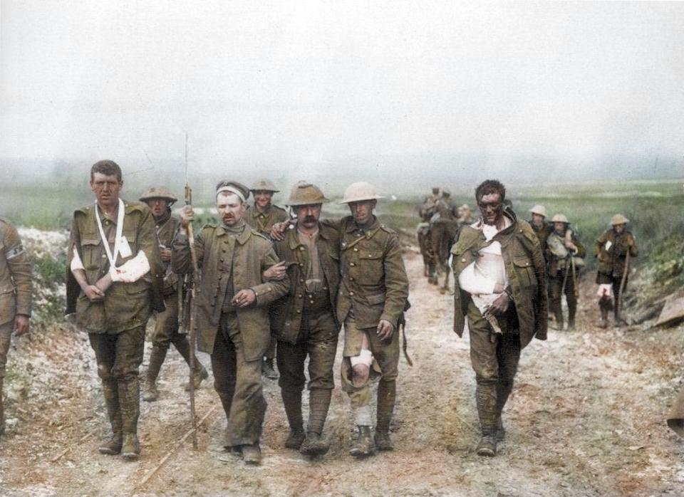 <p>A German prisoner assists wounded British solders head to a dressing station following fighting on Bazentin Ridge on July 19th, 1916 (Royston Leonard / Media Drum World / Caters News) </p>