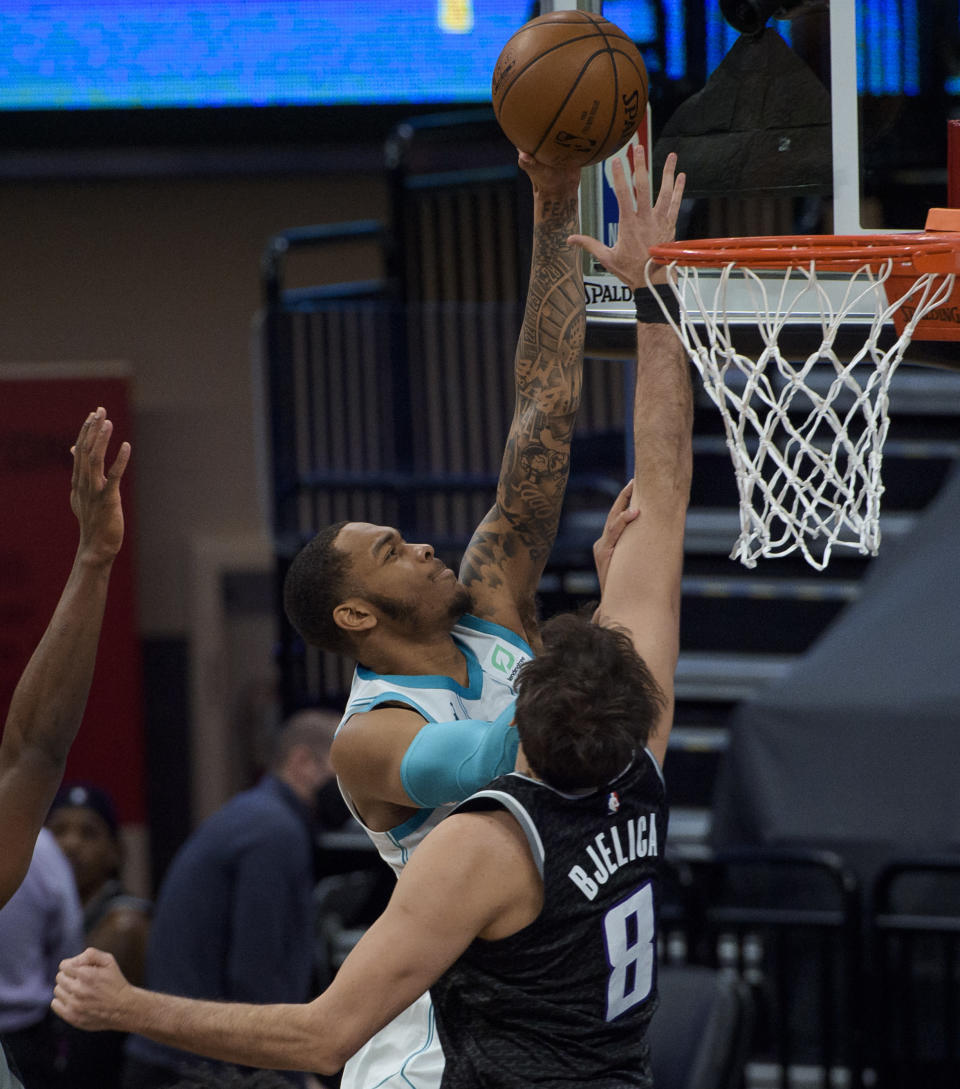 Charlotte Hornets forward P.J. Washington (25) scores over Sacramento Kings forward Nemanja Bjelica (8) during the second half of an NBA basketball game in Sacramento, Calif., Sunday, Feb. 28, 2021. The Hornets won 127-126. (AP Photo/Randall Benton)