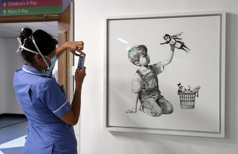 A member of staff takes a photograph of the new artwork painted by Banksy during lockdown, entitled 'Game Changer', which has gone on display to staff and patients on Level C of Southampton General Hospital.