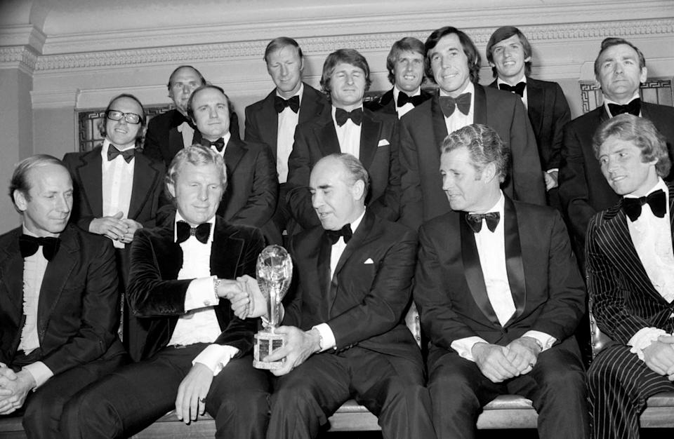 Standing (left to right): Nobby Stiles, Ray Wilson, George Cohen, Jackie Charlton, Roger Hunt, Geoff Hurst, Gordon Banks, Martin Peters, Les Cocker (assistant trainer). Sitting: Bobby Charlton, Bobby Moore, Ramsey, Harold Shepherdson (trainer), and Alan Ball. July 1974 74-4559-001 (Photo by Daily Mirror/Mirrorpix/Mirrorpix via Getty Images)