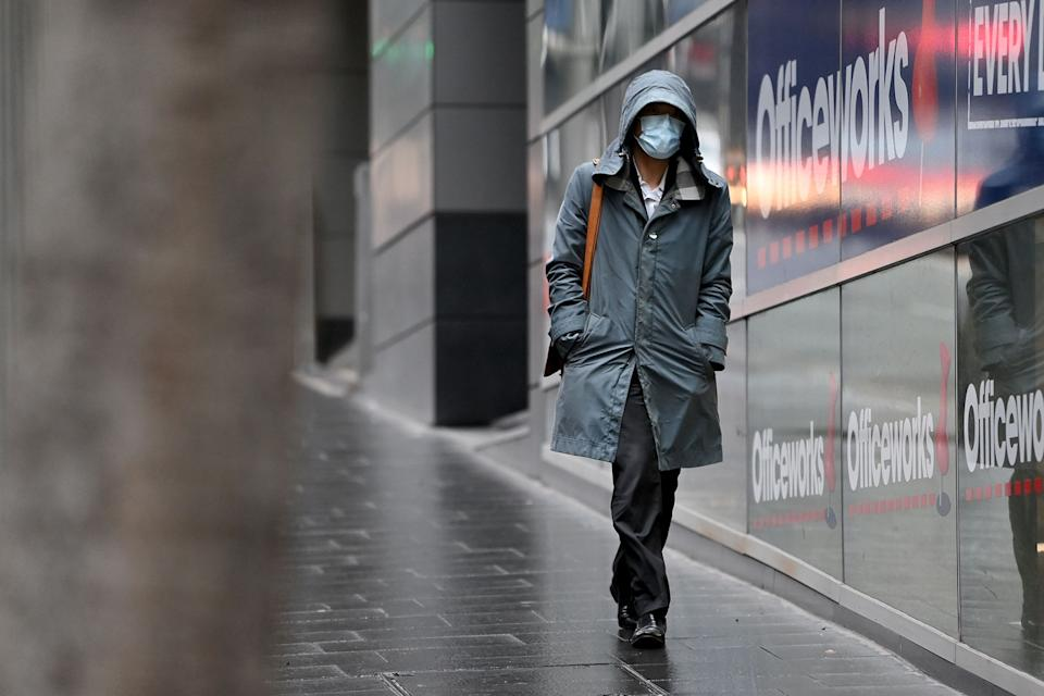 A person walks past Officeworks in Sydney wearing a face mask during the coronavirus pandemic.