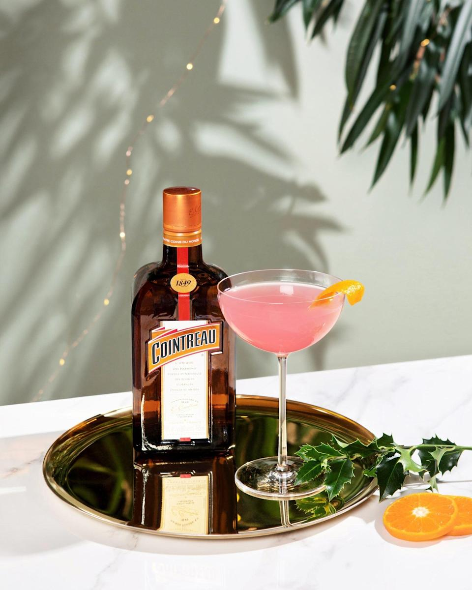 bottle of Cointreau and glass with pink cocktail on brass tray