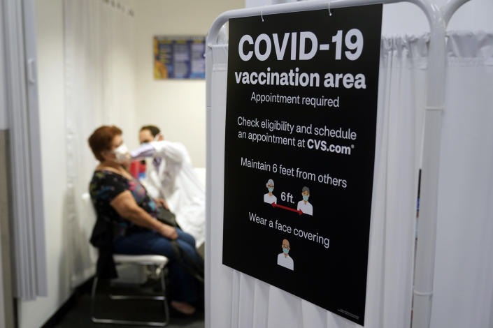FILE - In this March 1, 2021, file photo, a patient receives a shot of the Moderna COVID-19 vaccine next to a guidelines sign at a CVS Pharmacy branch in Los Angeles. More than 27 million Americans fully vaccinated against the coronavirus will have to keep waiting for guidance from U.S. health officials for what they should and shouldn't do. The Biden administration said Friday, March 5, it's focused on getting the guidance right and accommodating emerging science. (AP Photo/Marcio Jose Sanchez, File)