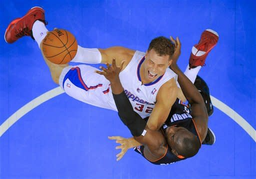Los Angeles Clippers forward Blake Griffin, top, drives to the basket over Charlotte Bobcats forward Bismack Biyombo during the first half of an NBA basketball game in Los Angeles, Tuesday, Feb. 26, 2013. (AP Photo/Chris Carlson)