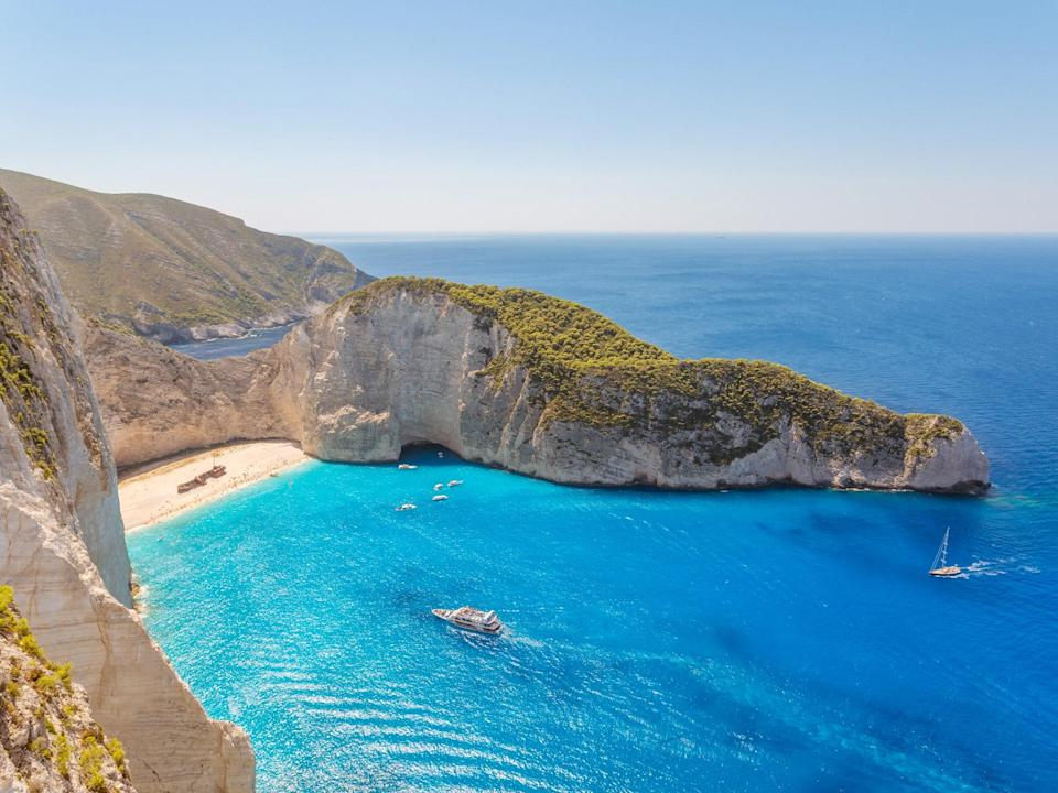 """Also known as Shipwreck Beach due to the ancient freighter buried at its center, Navagio is easily the <a href=""""https://www.cntraveler.com/galleries/2016-03-22/beautiful-beaches-in-greece?mbid=synd_yahoo_rss"""" rel=""""nofollow noopener"""" target=""""_blank"""" data-ylk=""""slk:most beautiful stretch of sand"""" class=""""link rapid-noclick-resp"""">most beautiful stretch of sand</a> in Greece. It's sheltered by sheer limestone cliffs and is so isolated that you can only access it by boat. While you could easily spend all day sunning on its powdery sands, its beauty is best appreciated from the viewing platform in the cliffs above—just follow the signs to the Agios Gergio Kremnao monastery."""