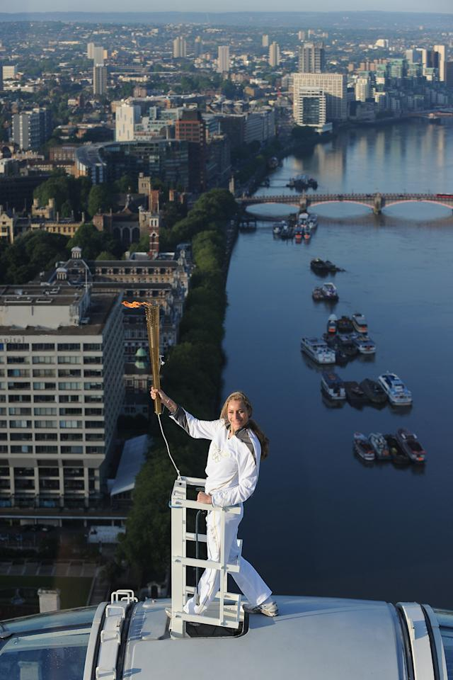 In this photo provided by LOCOG, Amelia Hempleman-Adams poses with the Olympic Flame on top of a London Eye pod on the Torch Relay leg through London. Opening Ceremonies for the 2012 London Olympics will be held Friday July 27. (AP Photo/LOCOG, Lewis Whyld)