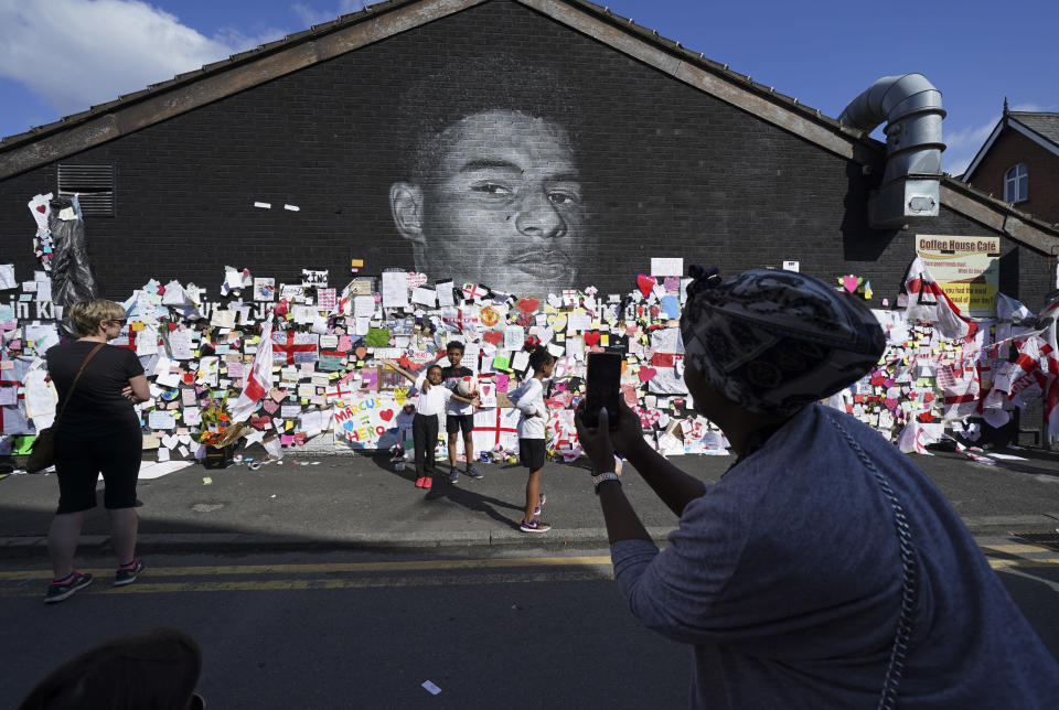A woman takes photos of children standing in front of the messages of support left on a mural of Manchester United striker and England player Marcus Rashford, on the wall of the Coffee House Cafe on Copson Street, in Withington, Manchester, England, Tuesday July 13, 2021. The mural was defaced with graffiti in the wake of England losing the Euro 2020 soccer championship final match to Italy. (AP Photo/Jon Super)