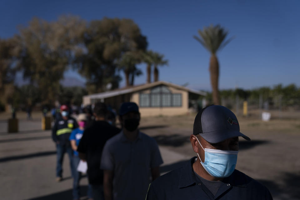 Hispanic farm workers wait in line to receive the Pfizer-BioNTech COVID-19 vaccine in Mecca, Calif., Thursday, Jan. 21, 2021. The farmworkers who got their shots are among the millions of immigrants around the United States, who advocacy groups warn may be some of the most difficult people to reach during the largest vaccination campaign in American history. (AP Photo/Jae C. Hong)