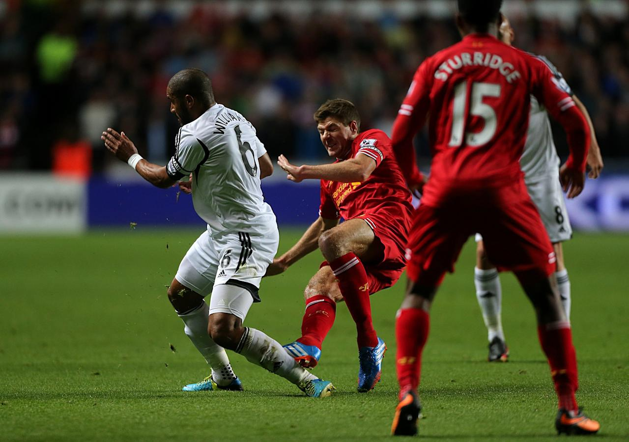 Liverpool's Steven Gerrard (centre) and Swansea City's Ashley Williams battle for the ball