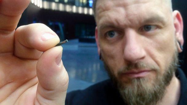 FILE - In this March 14, 2017, file photo, Jowan Osterlund from Biohax Sweden, holds a small microchip implant, similar to those implanted into workers at the Epicenter digital innovation business center during a party at the co-working space in cent (The Associated Press)