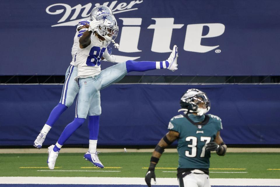 Dallas Cowboys wide receiver CeeDee Lamb (88) and wide receiver Amari Cooper, rear, celebrate a touchdown catch by Lamb as Philadelphia Eagles cornerback Grayland Arnold (37) walks away in the second half of an NFL football game in Arlington, Texas, Sunday, Dec. 27. 2020. (AP Photo/Michael Ainsworth)