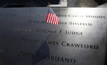 FILE - In this Monday, Sept. 12, 2011 file photo, a U.S. flag is stuck into the etched name of Father Mychal F. Judge, the New York Fire Department chaplain who died in the 9/11 attacks on the World Trade Center, at the National September 11 Memorial in New York. (AP Photo/Mike Segar, Pool, File)