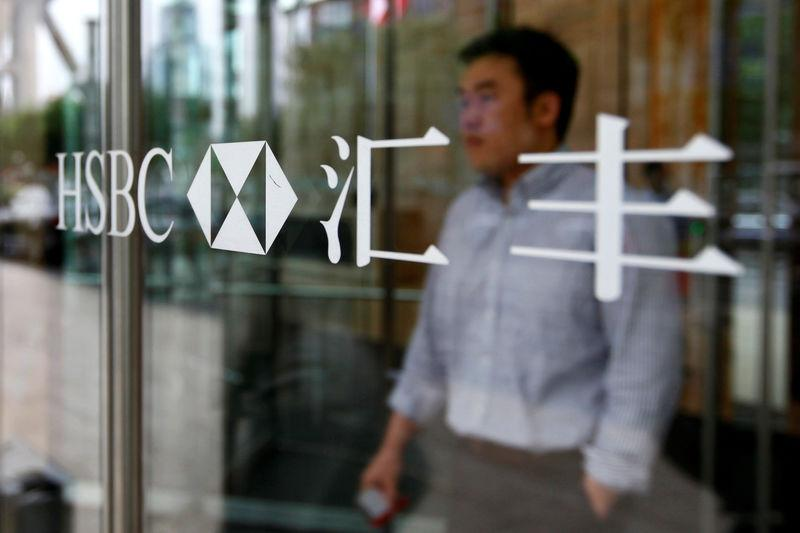 FILE PHOTO: A man walks past the HSBC logo at the bank's new China headquarters in Shanghai