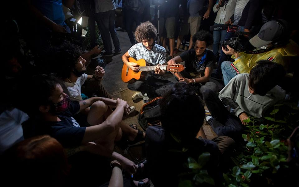A man plays a guitar during the protests - Yander Zamora/EPA-EFE/Shutterstock