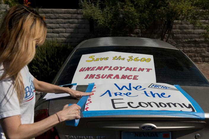 Francis Stallings tapes signs to her car before participating in a caravan rally down the Las Vegas Strip in support of extending the $600 unemployment benefit, August 6, 2020 in Las Vegas, Nevada. (Photo by BRIDGET BENNETT/AFP via Getty Images)