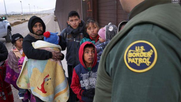 PHOTO: A U.S. Border Patrol agent speaks with Central American immigrants at the U.S.-Mexico border fence on Feb. 01, 2019, in El Paso, Texas. (John Moore/Getty Images)