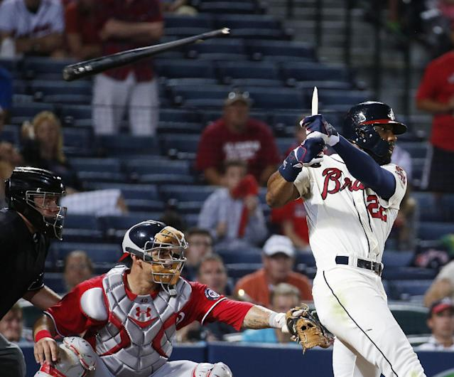 Atlanta Braves' Jason Heyward breaks his bat as he drives in a run with a sacrifice fly in the sixth inning of a baseball game, in front of Washington Nationals catcher Wilson Ramos early Sunday, Aug. 10, 2014, in Atlanta. (AP Photo/John Bazemore)