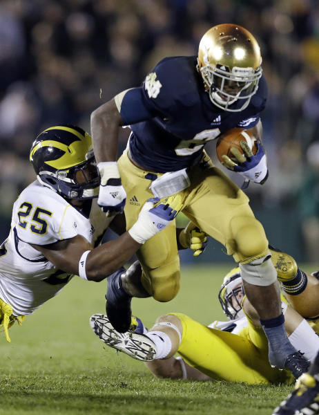 FILE - In this Sept. 22, 2012, file photo, Notre Dame's Theo Riddick (6) runs out of the attempted tackle of Michigan's Kenny Demens (25) during the second half of an NCAA college football game in South Bend, Ind. With the national championship on the line, two throwback offenses will slug it out. No. 1 Notre Dame and No. 2 Alabama rely heavily on the run, and that doesn't figure to change in the biggest game of the year. (AP Photo/Darron Cummings, File)