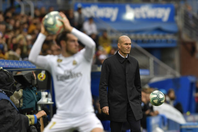 Real Madrid's Gareth Bale holds up the ball as Real Madrid's head coach Zinedine Zidane looks on during the Spanish La Liga soccer match between Real Madrid and Alaves at Mendizorroza stadium, in Vitoria, northern Spain, Saturday, Nov. 30, 2019. (AP Photo/Alvaro Barrientos)