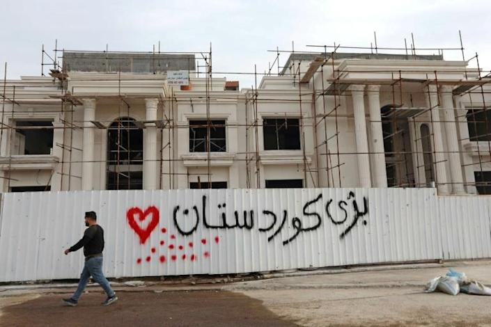 """A man walks past a graffiti reading """"Long live Kurdistan"""" near the scene of a rocket attack blamed on Iranian-linked Iraqi paramilitaries against US-led coalition forces in Arbil on February 16, 2021"""