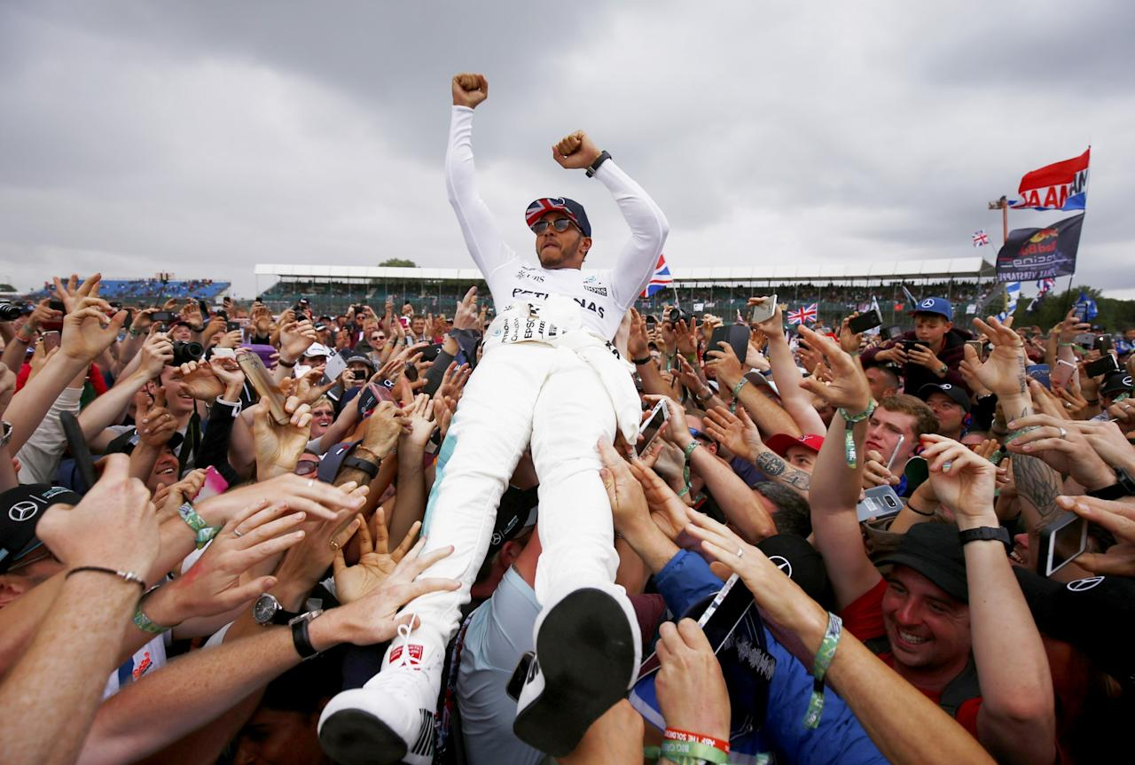 <p>Victory: Lewis Hamilton is carried by his supporters at Silverstone after winning the British Grand Prix. (Getty) </p>