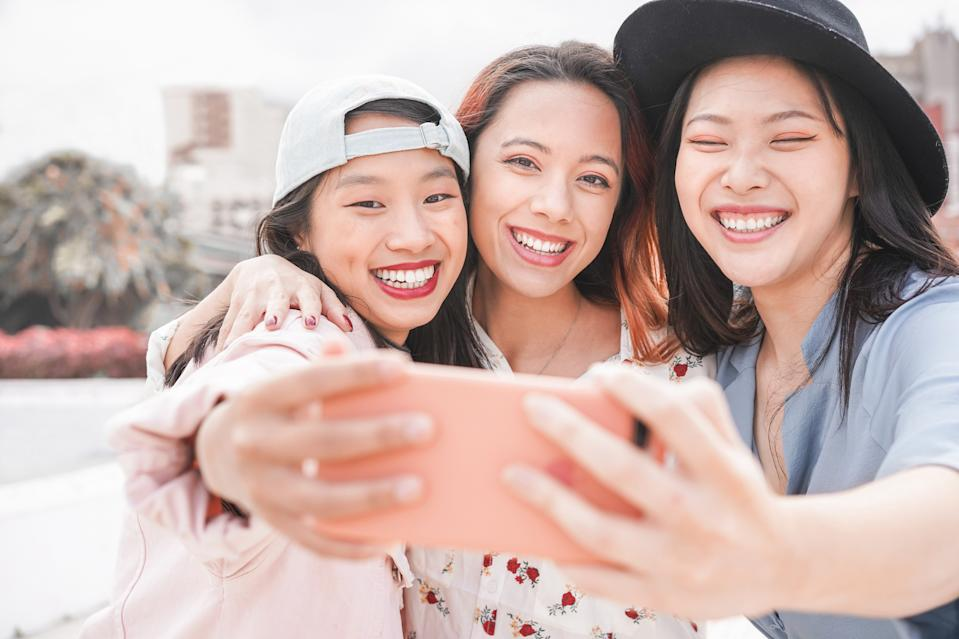 Portrait Of Happy Friends Taking Selfie With Smart Phone While Standing Outdoors
